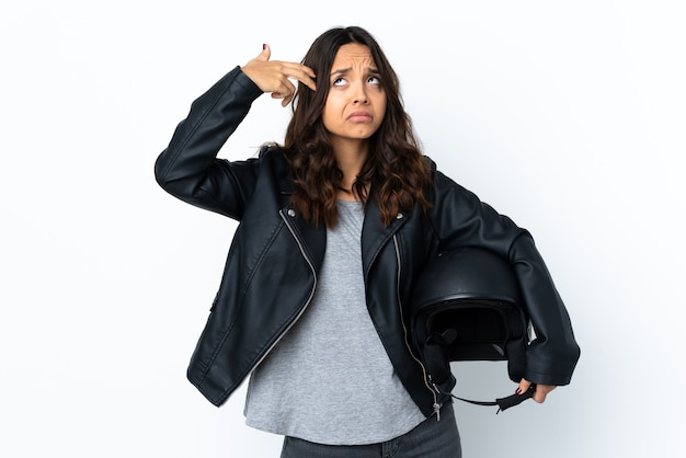 Jeune femme tenant un casque de moto sur fond blanc isolé avec des problèmes de geste de suicide