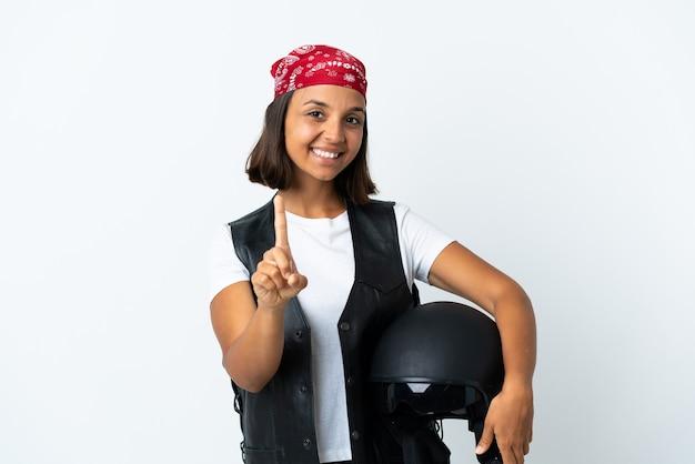 Jeune femme tenant un casque de moto isolé sur blanc montrant et soulevant un doigt