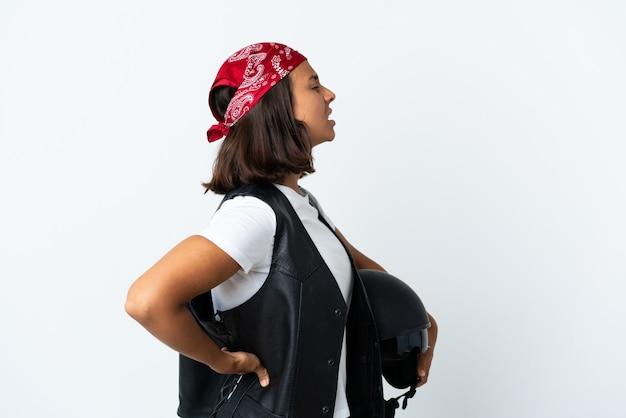 Jeune femme tenant un casque de moto isolé sur blanc souffrant de maux de dos pour avoir fait un effort