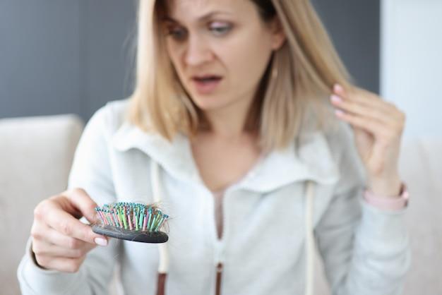 Jeune femme tenant les cheveux et regardant le peigne avec surprise. concept de traitement de la perte de cheveux