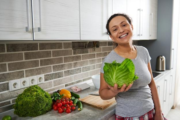 Jeune femme tenant le chou dans sa main et souriant avec un sourire à pleines dents, regardant la caméra, debout contre le de la cuisine à la maison