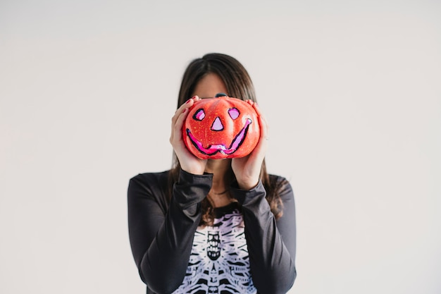 Jeune femme tenant une citrouille couvrant son visage. portant un costume squelette noir et blanc. concept d'halloween. à l'intérieur. mode de vie