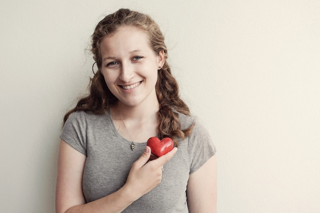 Jeune femme tenant coeur rouge, assurance maladie, notion de don