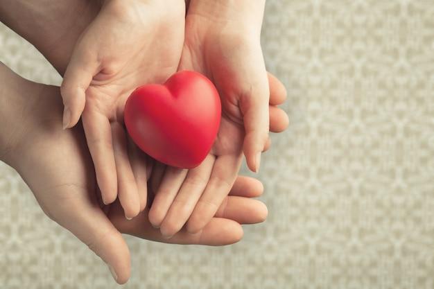 Jeune femme tenant coeur rouge, assurance maladie,
