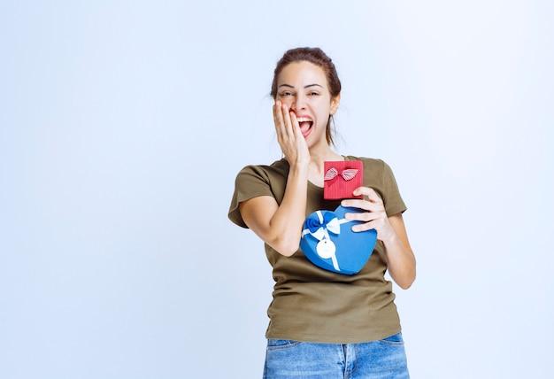 Jeune femme tenant des coffrets cadeaux bleus en forme de coeur et rouge et les appréciant