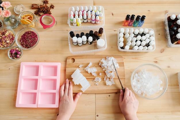 Jeune femme tenant un couteau sur des cristaux de masse de savon dur tout en le coupant à bord parmi les ingrédients aromatiques