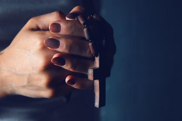 Jeune femme tenant une croix en bois