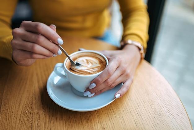 Jeune femme tenant la cuillère à café et en remuant le café chaud sur la table en bois. fermer.