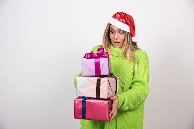Jeune femme tenant dans les mains des cadeaux de noël festifs
