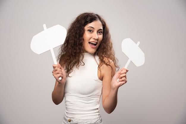 Jeune femme tenant deux affiches blanches vierges. photo de haute qualité