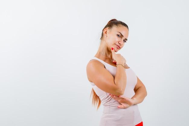Jeune femme tenant le doigt sur le menton en maillot et regardant pensif, vue de face.