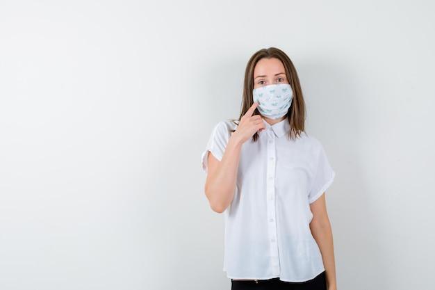 Jeune femme tenant le doigt sur son masque et regardant pensive