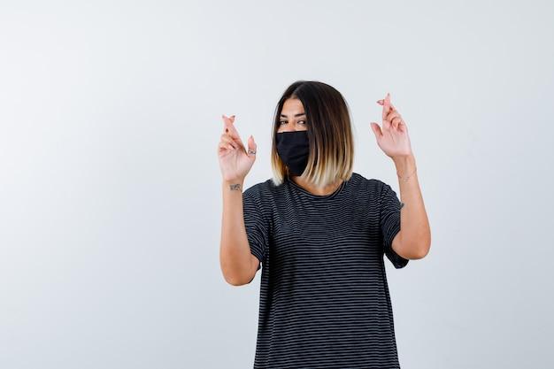 Jeune femme tenant les doigts croisés en robe noire, masque noir et air heureux. vue de face.