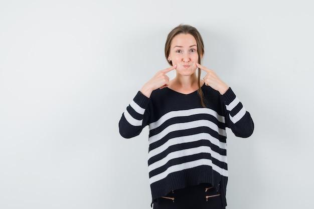Jeune femme tenant les doigts sur les joues soufflées en chemise décontractée et à la drôle