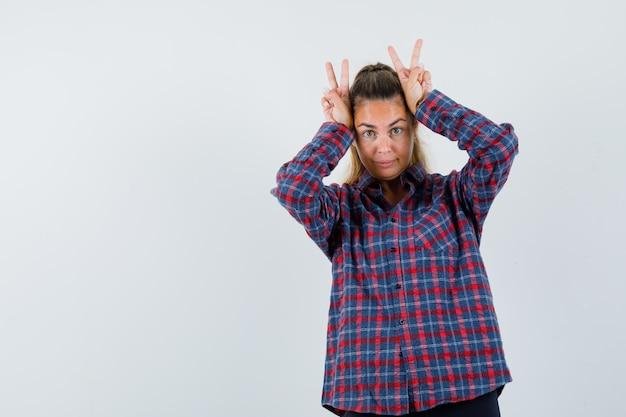 Jeune femme tenant les doigts sur la tête comme montrant le geste de paix en chemise à carreaux et à la jolie