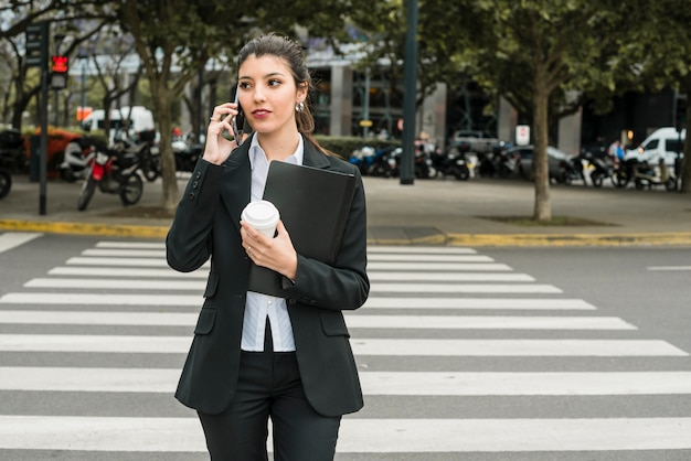 Jeune femme tenant un dossier et emporter une tasse de café en traversant la route