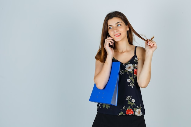 Jeune femme tenant un dossier, parlant au téléphone portable, faisant tournoyer les cheveux autour de ses doigts en blouse, jupe et l'air gai. vue de face.