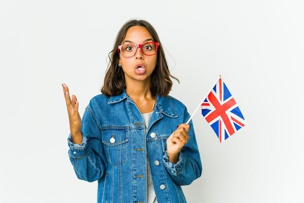 Jeune femme tenant un drapeau anglais célébrant une victoire ou un succès