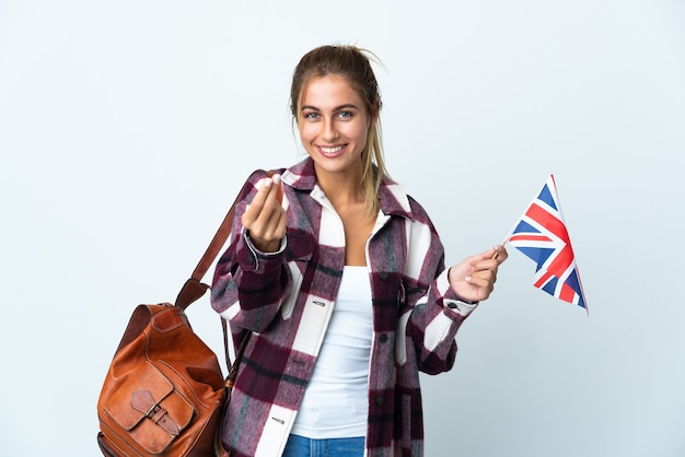 Jeune femme tenant un drapeau britannique isolé sur un espace blanc faisant le geste de l'argent