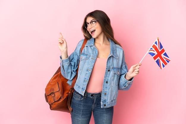 Jeune femme tenant un drapeau du royaume-uni isolé sur fond rose dans l'intention de réaliser la solution tout en soulevant un doigt