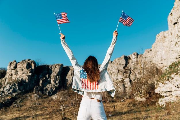 Jeune femme tenant des drapeaux américains au-dessus de la tête