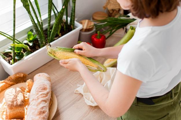 Jeune femme tenant du maïs biologique