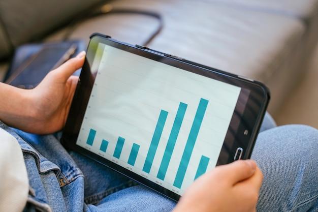 Jeune femme tenant un écran numérique avec le graphique statistique en grandissant.