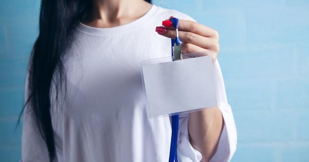 Jeune femme tenant une étiquette d'identification