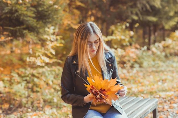 Jeune femme tenant des feuilles d'automne dans le parc d'automne. concept saisonnier, style de vie et loisirs.