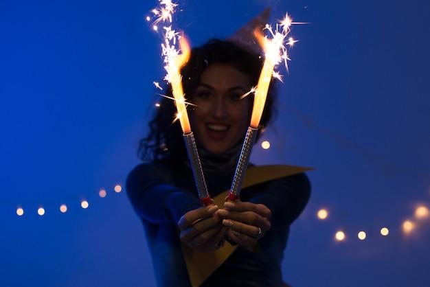 Jeune femme tenant des feux d'artifice. vacances, événement, célébration