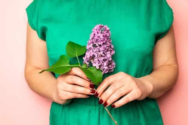 Jeune femme tenant des fleurs lilas