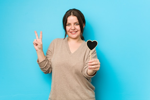 Jeune femme tenant une forme de coeur montrant le numéro deux avec les doigts.