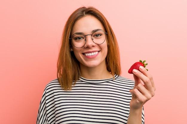Jeune femme tenant une fraise heureuse, souriante et gaie.
