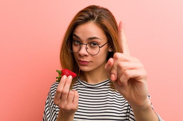 Jeune femme tenant une fraise montrant le numéro un avec le doigt.