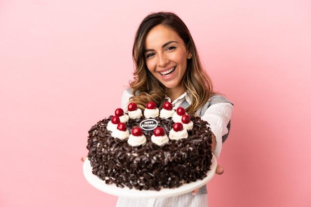 Jeune femme tenant un gâteau d'anniversaire sur fond rose isolé