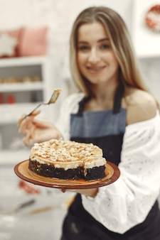 Jeune femme tenant un gâteau dans la cuisine