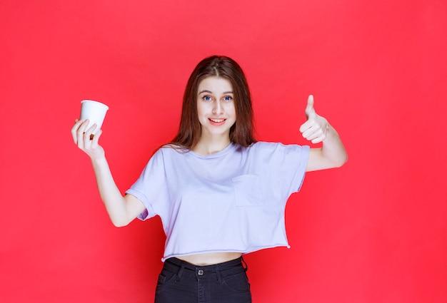 Jeune femme tenant un gobelet à eau jetable blanc et montrant un signe de satisfaction.