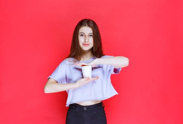 Jeune femme tenant un gobelet à eau jetable blanc.