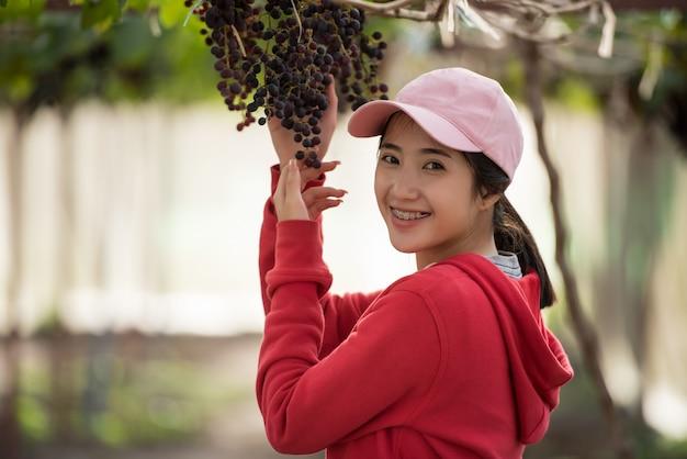 Jeune femme tenant une grappe de raisin