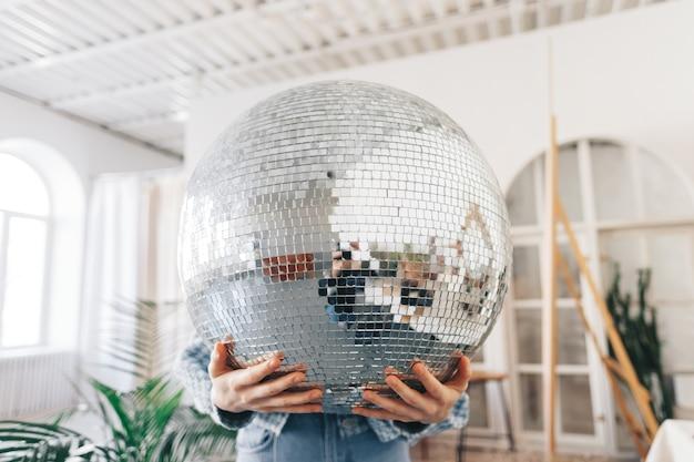 Jeune femme tenant une grosse boule disco dans les mains.