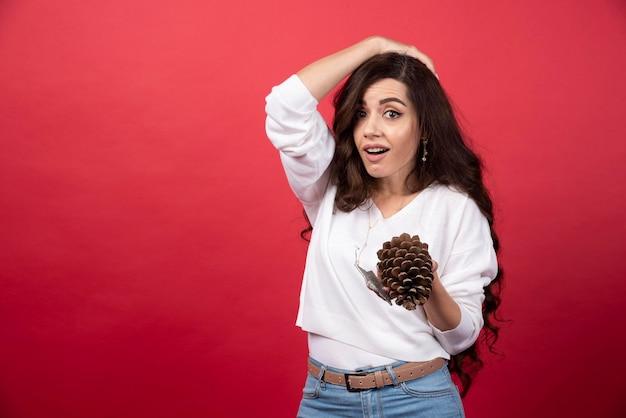 Jeune femme tenant une grosse pomme de pin de noël sur fond rouge. photo de haute qualité