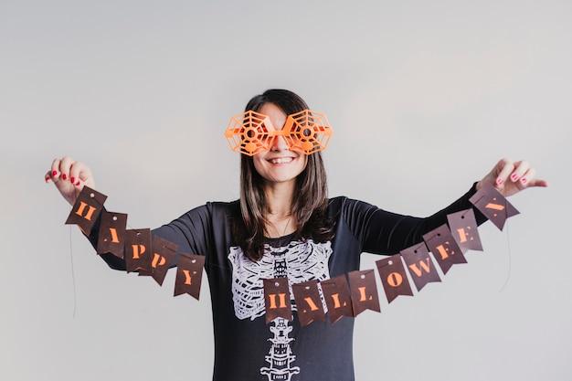 Jeune femme tenant une guirlande avec signe d'halloween heureux. lifestyle à l'intérieur. costume de squelette