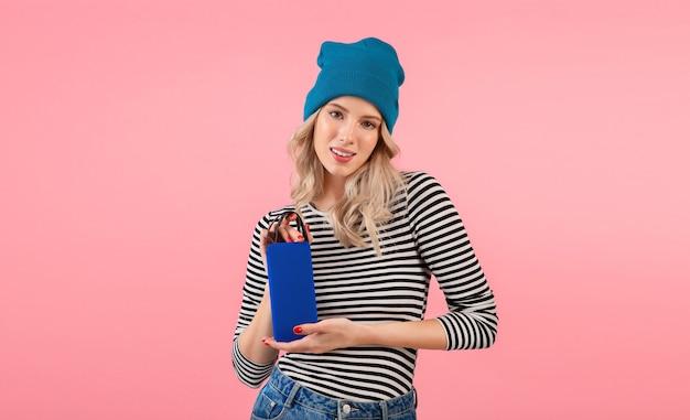 Jeune femme tenant haut-parleur sans fil écouter de la musique portant une chemise rayée et un chapeau bleu souriant posant sur rose