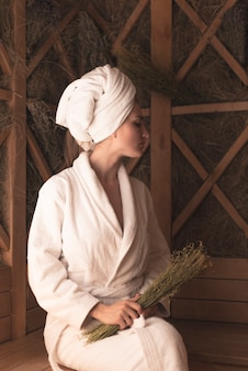 Jeune femme tenant des herbes médicinales se détendre dans le sauna