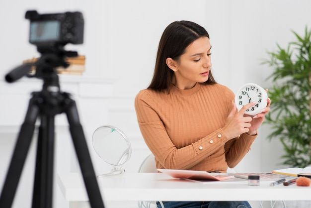 Jeune femme tenant une horloge à la caméra