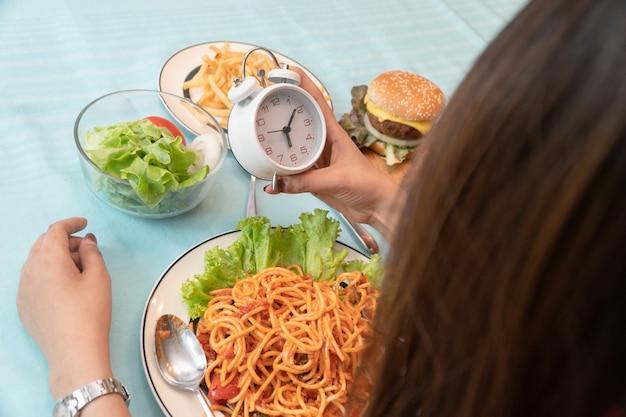 Jeune femme tenant une horloge et prêt à manger un dîner