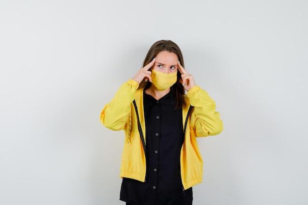 Jeune femme tenant l'index sur les tempes