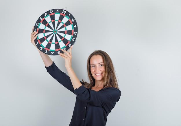 Jeune femme tenant un jeu de fléchettes en chemise noire et à la joyeuse