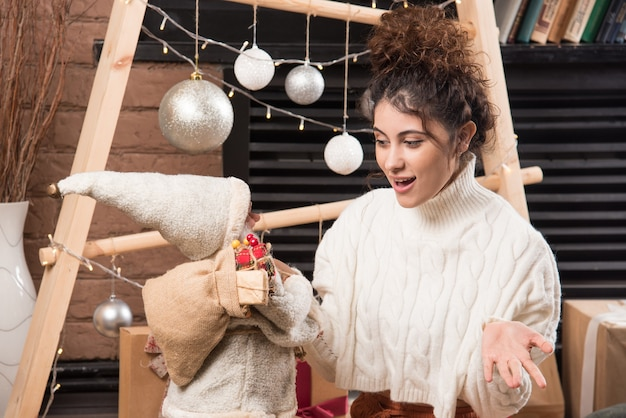 Jeune femme tenant un jouet du père noël