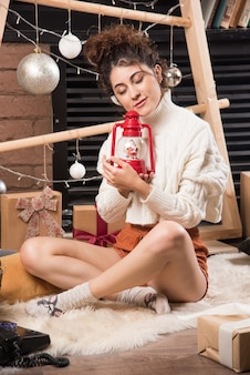 Jeune femme tenant une lampe de noël rouge